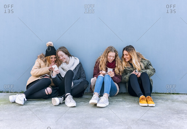 Four friends sitting side by side on the ground looking at cell phones