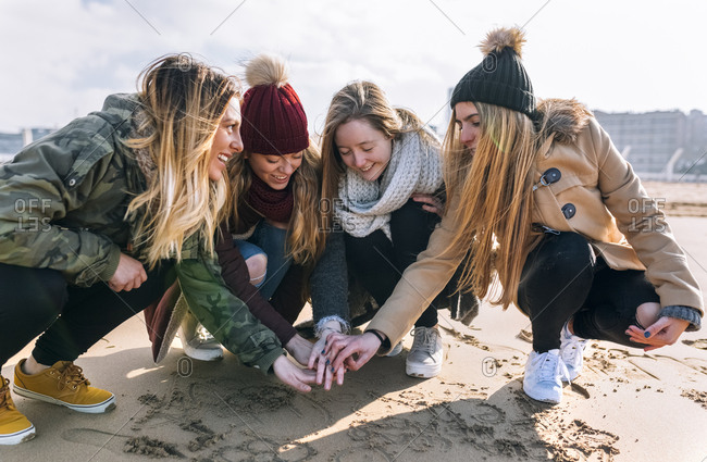 Four friends joining hands on the beach