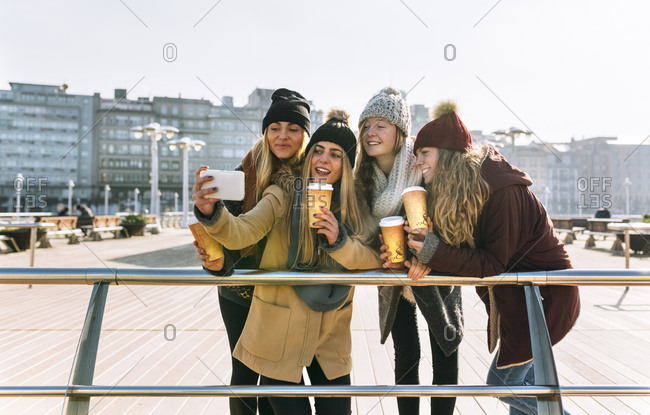 Four friends with coffee to go taking a selfie with smartphone