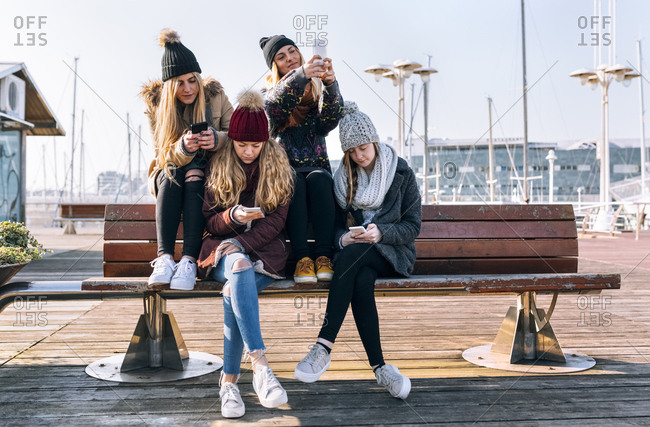 Four young women sitting on a bench using their cell phones