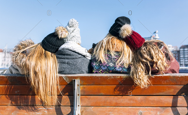 Back view of four friends sitting on a bench in winter