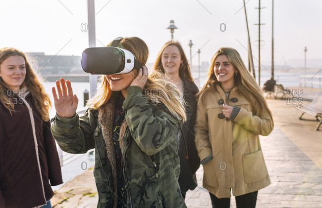 Teenage girl using wearing VR glasses while her friends watching her