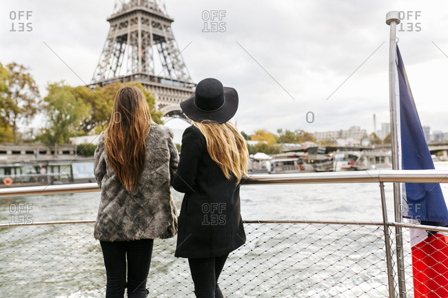 Paris- France- two tourists taking a cruise on Seine River with Eiffel Tower in the background