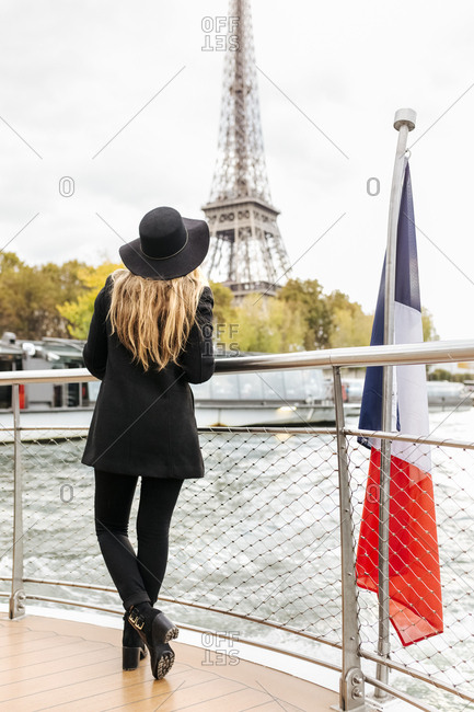Paris- France- back view of tourist taking a cruise on Seine River looking at Eiffel Tower