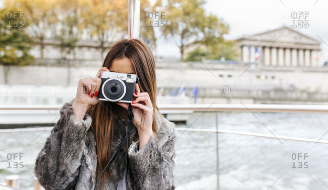 Paris- France- tourist taking picture with camera on Seine River