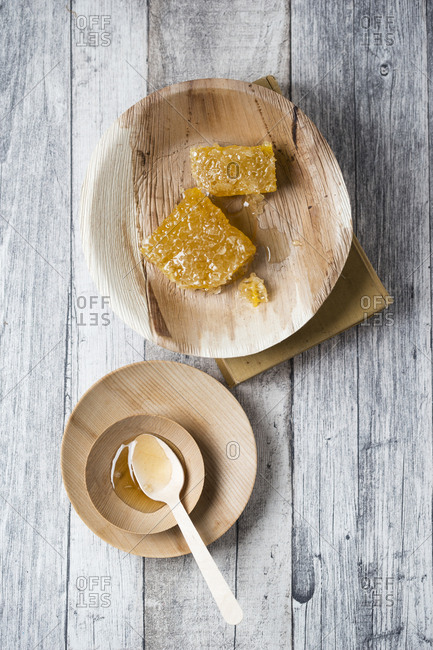 Honeycombs and honey on wooden plates