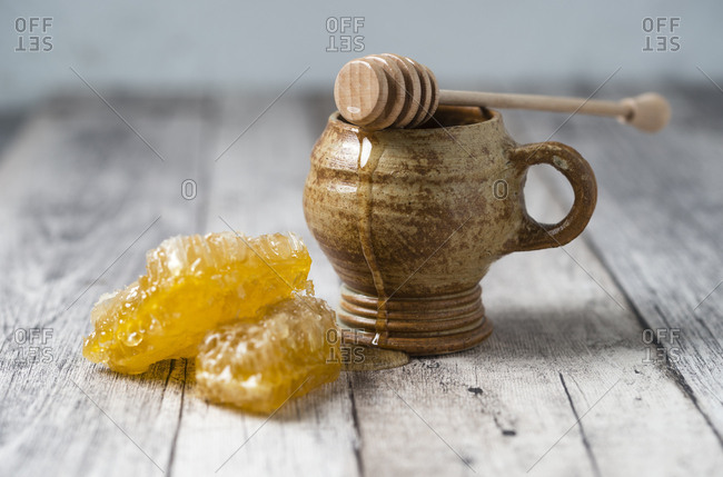 Honeycombs- clay pot and honey dipper on wood