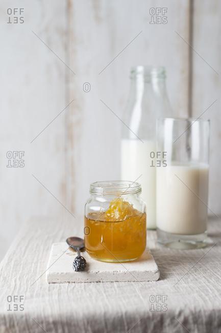 Honey jar with honeycomb and milk