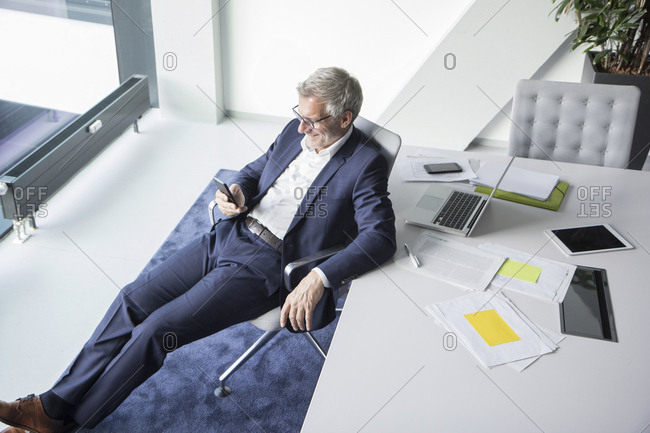 Smiling businessman using cell phone in office