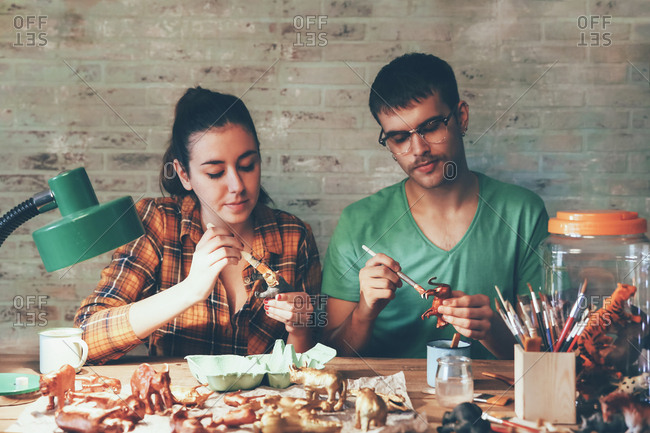 Young couple painting animal figurines with paint