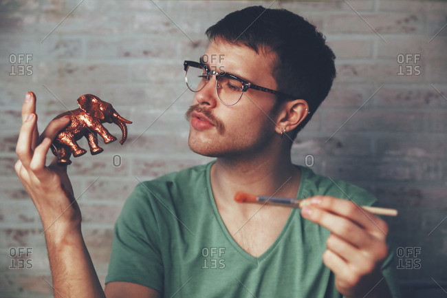 Young man painting plastic elephant figure with copper paint