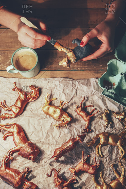 Overhead view of woman painting animal figurines with paint