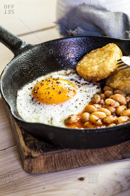 Fried egg- baked beans and hash browns in frying pan on wooden board