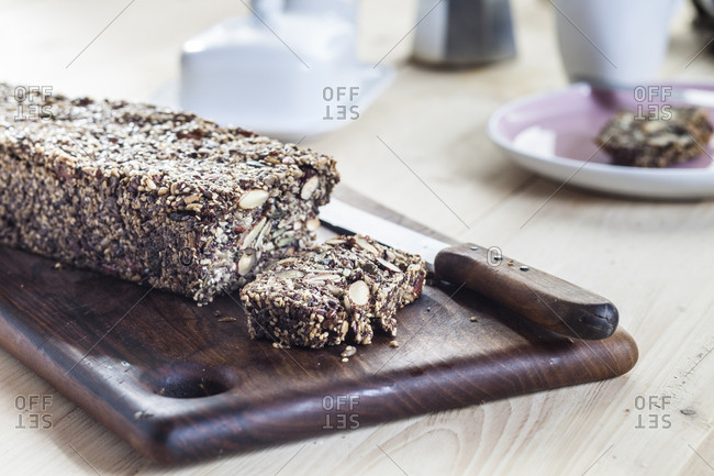 Home-baked whole meal gluten-free bread with nuts and seeds on wooden board