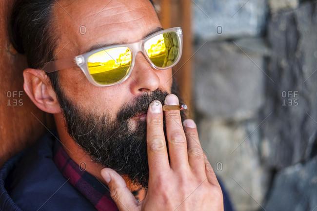 Portrait of man wearing mirrored sunglasses smoking cigarillo