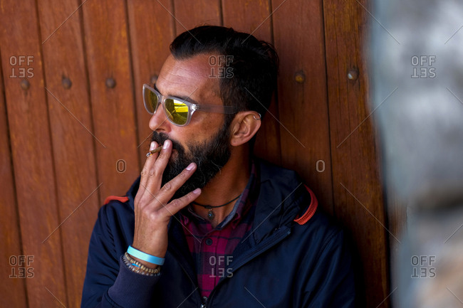 Portrait of man wearing mirrored sunglasses smoking cigarillo