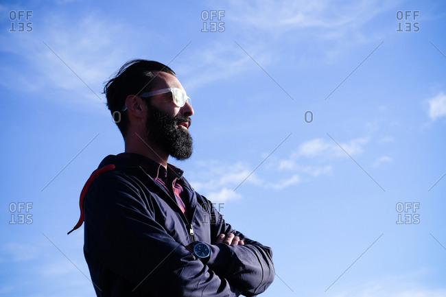 Portrait of man with full beard and sunglasses in front of sky