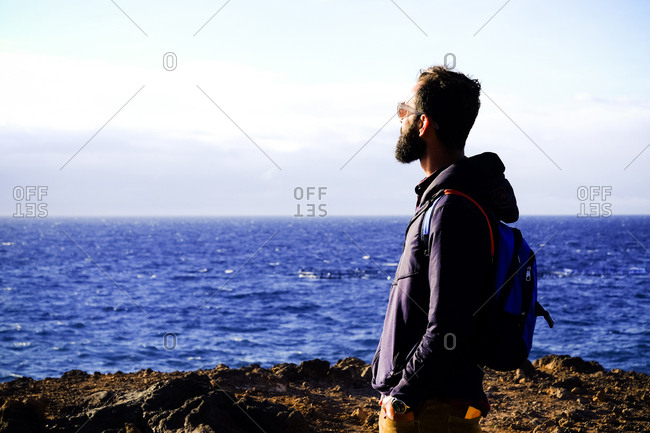 Man with backpack looking at the sea