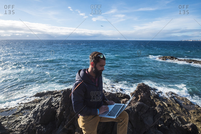 Spain- Tenerife- man using laptop in front of the sea