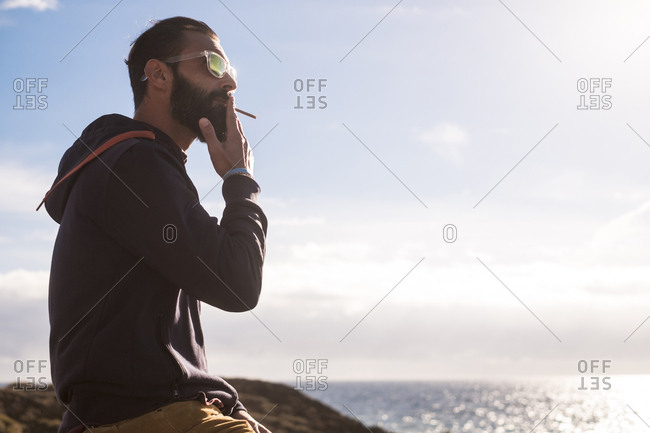 Portrait of man smoking cigarillo while looking at the sea