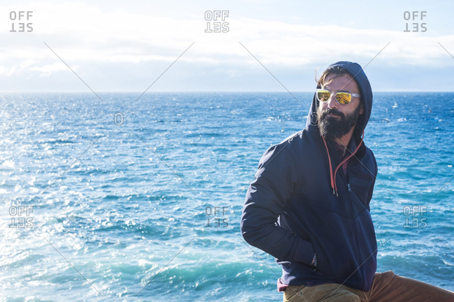Portrait of man wearing mirrored sunglasses and hooded jacket in front of the sea