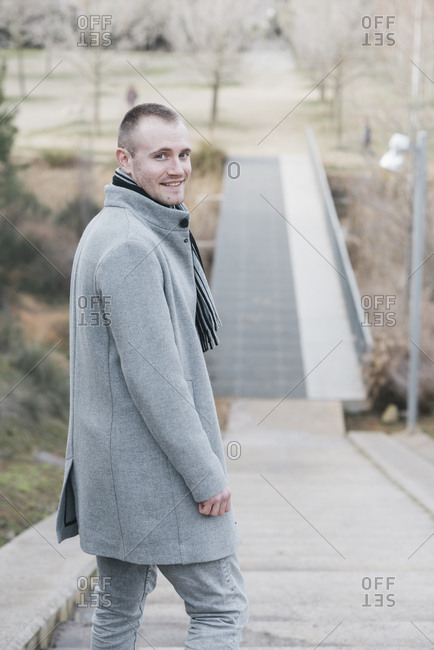 Portrait of smiling man on stairs in a park