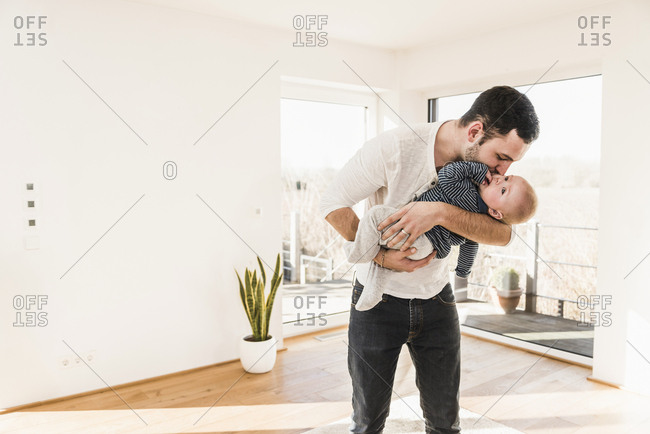 Father holding and hugging his baby son- standing in comfortable home
