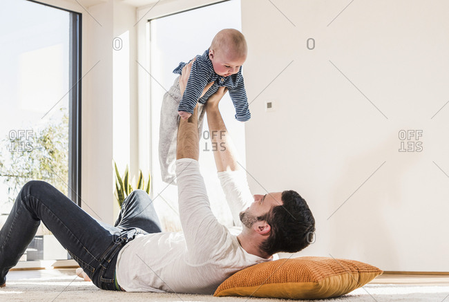 Father playing with baby son- lying on carpet