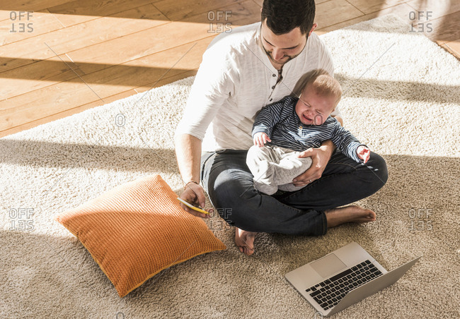 Father sitting cross-legged with baby son on lap- using laptop and smart phone