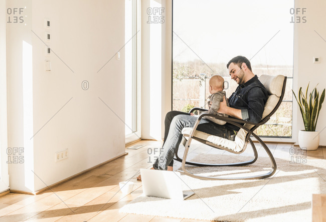 Father sitting in arm chair with baby son on lap