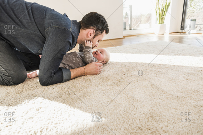 Father and baby son playing on carpet at home