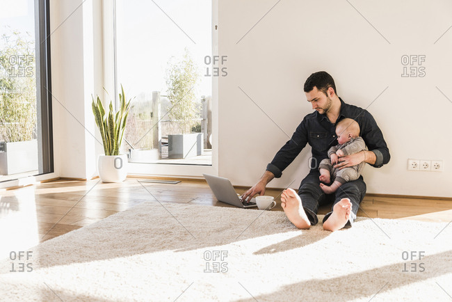 Father with baby son using laptop sitting on floor