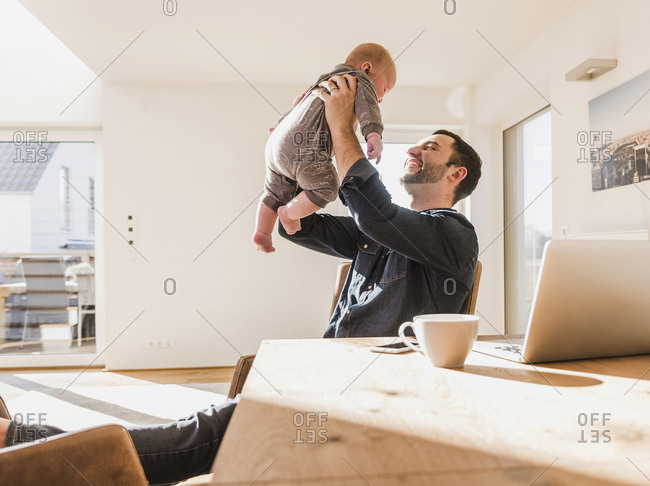 Father sitting at home playing with baby son