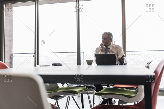 Senior manager in office using laptop looking worried