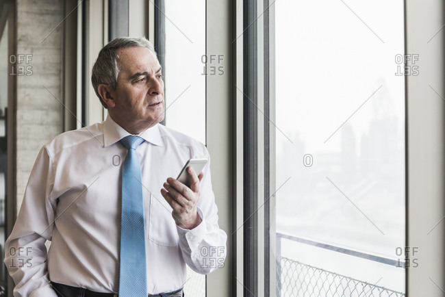 Senior manager in office standing at window using smart phone