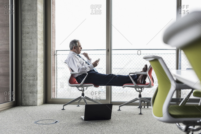 Senior manager in office sitting on chairs with feet up talking on the phone