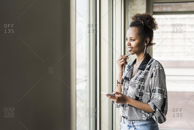 Young woman standing at window using smart phone