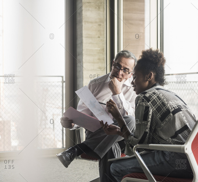 Senior manager discussing documents with young coworker
