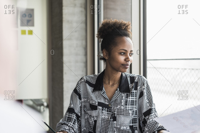 Young g woman sitting in office- looking away