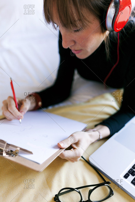 Young woman lying on bed writing on clipboard