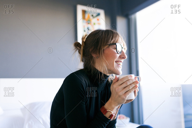 Happy young woman at home drinking cup of coffee