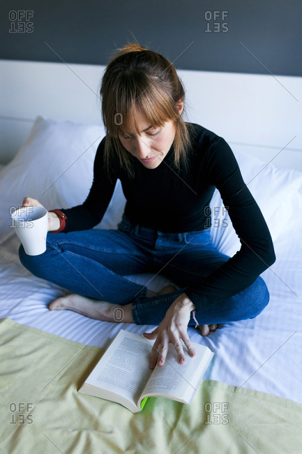 Young woman sitting on bed drinking cup of coffee and reading a book