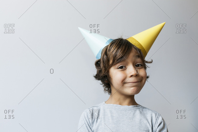 Portrait of little boy with two party hats on his head