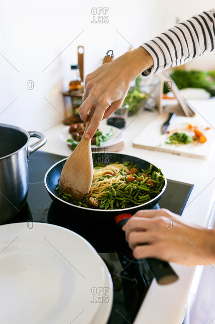 Young woman cooking vegan pasta in her kitchen