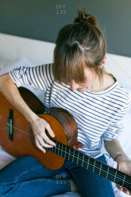 Young woman playing guitar- sitting on bed