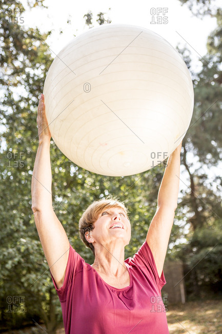 Senior woman exercising with fitness ball outdoors