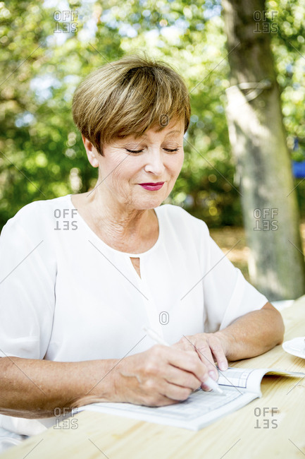 Senior woman doing a crossword puzzle outdoors