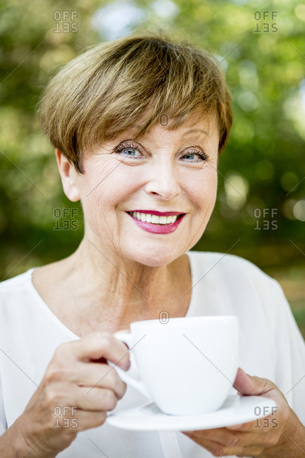 Portrait of smiling senior woman drinking cup of coffee outdoors