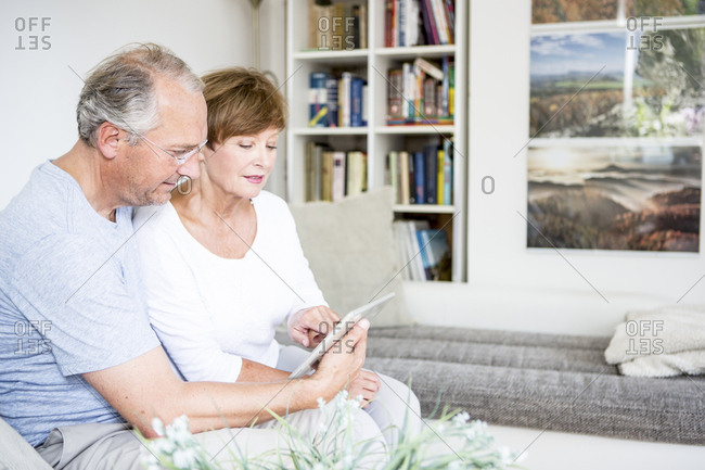 Senior couple at home sitting on couch using digital tablet