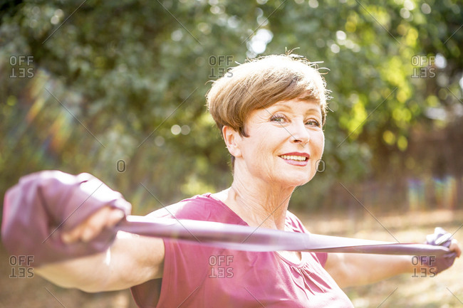 Portrait of smiling senior woman exercising with resistance band outdoors